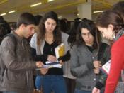 Fotografia de alunos procuram informações junto a uma banca no átrio do C3