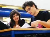 Estudantes sentados, junto a uma mesa
