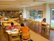 Pessoas estudam numa mesa na biblioteca