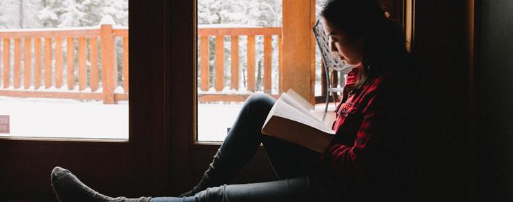 Jovem a ler um livro perto de uma janela