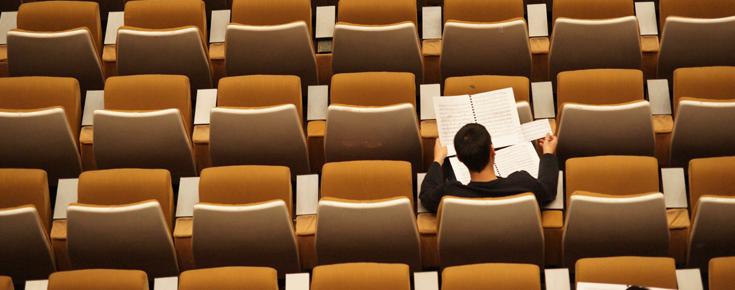 Anfiteatro com várias cadeiras e uma pessoa sentada a ler