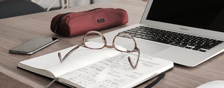 Fotografia de uma secretária, com um computador portátil, caderno, estojo, telemóvel e óculos